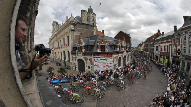 A fisheye view shows spectators as they take pictures from a window of the pack passing through Aire-sur-la-Lys during the third stage of the Tour de France cycling race over 197 kilometers (122.4 miles) with start in Orchies and finish in Boulogne-sur-Mer, northern France, Tuesday July 3, 2012. (AP Photo/Christophe Ena)
