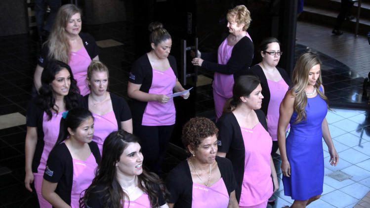 Dr Kirsti Funk, far right, walks in front of nurses from the Pink Lotus Breast Center, before making a statement regarding Angelina Jolie's double mastectomy Tuesday May 14, 2013 in Beverly Hills,  Calif. Jolie underwent the procedure after learning she had a high probability for breast cancer.  ( AP Photo/Nick Ut)