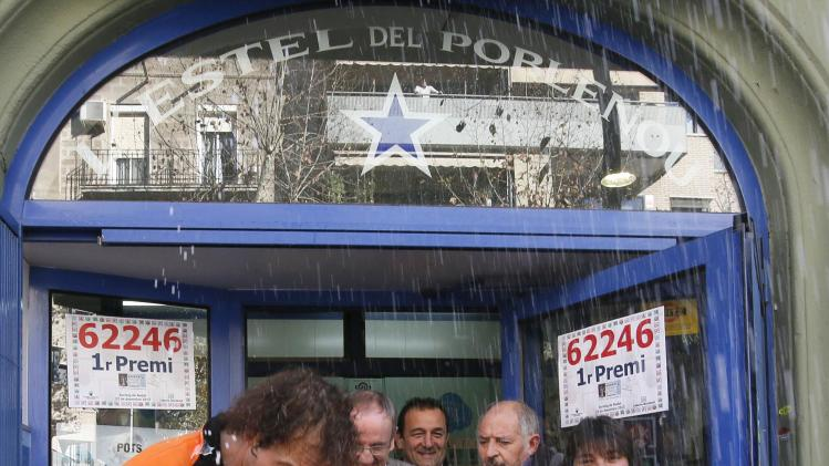 "People spray a bottle of cava and hold posters of the winning number to the first prize of ""El Gordo"" at a lottery shop where the number was sold in Barcelona"