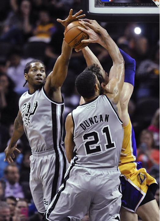 San Antonio Spurs' Kawhi Leonard, left, and Tim Duncan defend Los Angeles Lakers center Pau Gasol of Spain during the first half of an NBA basketball game Friday, March 14, 2014