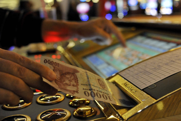 A man inserts a bill into a slot machine roulette in a gambling hall in Budapest, Hungary, Wednesday, Oct. 3, 2012. Hungarys ban on slot machines has taken the countrys gambling industry by surprise. On Tuesday, just over 24 hours after the announcement, lawmakers in the Hungarian Parliament voted in favor of a new bill which bans the country&#39;s slot machines. (AP Photo/Bela Szandelszky)