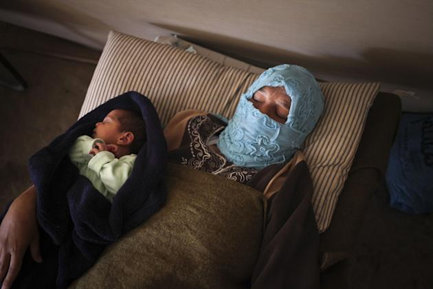 FILE - In this Monday, May 6, 2013, file photo, Syrian refugee Um Raad, 30, from Daraa, holds her 6 day-old son, Abdullah, at the Moroccan field hospital in Zaatari refugee camp near the Syrian border