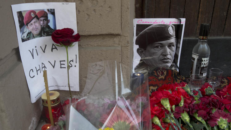 Candles, flowers and traditional Russian bottle of vodka,  placed next to an image of  Venzuela's late President Hugo Chavez outside the Venezuela's embassy in Moscow on Wednesday, March 6, 2013. Venezuela's Vice President Nicolas Maduro announced that Chavez died on Tuesday at age 58 after a nearly two-year bout with cancer. (AP Photo/Misha Japaridze)