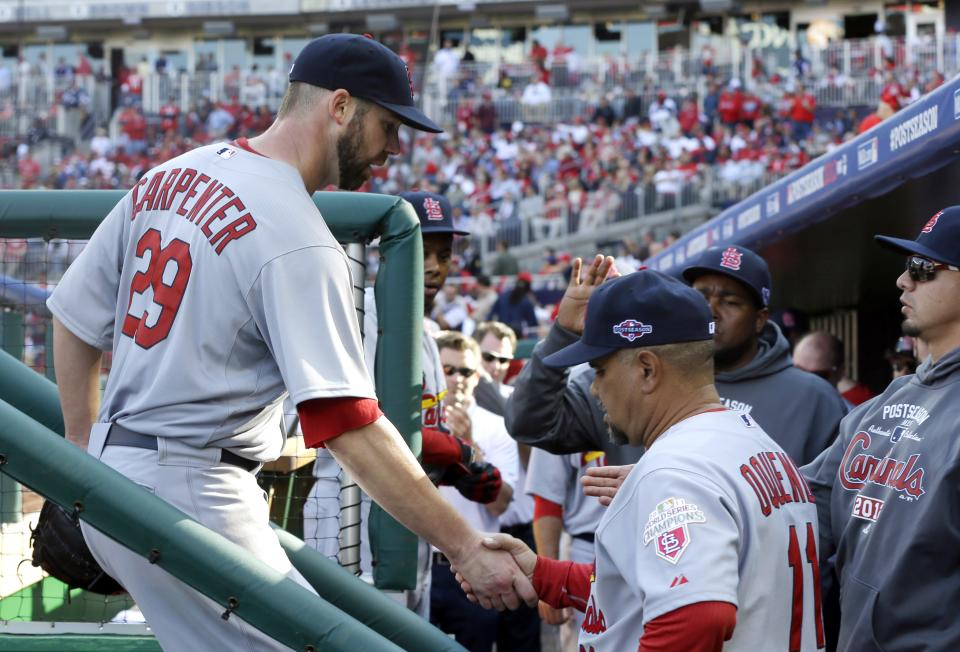St. Louis Cardinals starting pitcher Chris Carpenter, left, is greeted by third base coach Jose Oquendo and teammates in the dugout after being relieved in the sixth inning of Game 3 of the National League division baseball series against the Washington Nationals on Wednesday, Oct. 10, 2012, in Washington. (AP Photo/Pablo Martinez Monsivais)