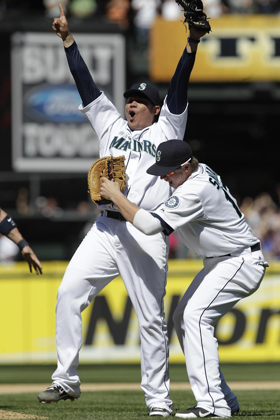 Seattle Mariners pitcher Felix Hernandez is congratulated by teammate Justin Smoak, right, after throwing a perfect game to end the ninth inning of baseball game against the Tampa Bay Rays, Wednesday, Aug. 15, 2012, in Seattle. The Mariners won 1-0. (AP Photo/Ted S. Warren)