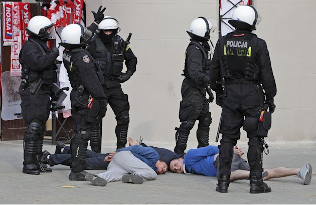 Police guard handcuffed men after they arrested them prior to the Euro 2012 soccer championship Group A match between Poland and Russia in Warsaw, Poland, Tuesday, June 12, 2012. Russian soccer fans c