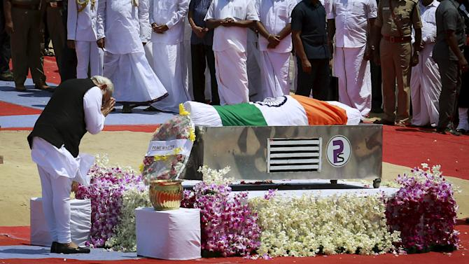 Indian Prime Minister Narendra Modi gestures after placing a wreath on the body of former President A.P.J. Abdul Kalam, wrapped with the national flag, during the funeral ceremony in Rameswaram