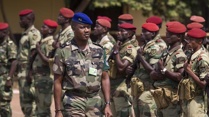 """Jean Felix Akaga, who heads a 10-nation regional force, inspects a contingent of forces from Gabon operating under the multinational central-African regional mandate, as they parade at their headquarters in the capital Bangui, Central African Republic, Wednesday, Jan. 2, 2013. Akaga says the town of Damara, about 70km (44 miles) north of the capital, is a """"red line that the rebels cannot cross"""" or his forces will attack. (AP Photo/Ben Curtis)"""