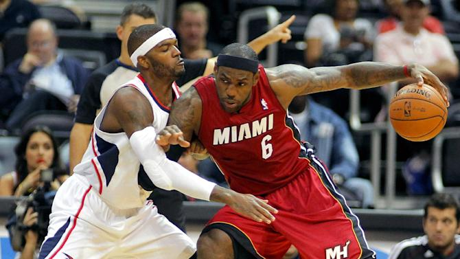 Miami Heat forward LeBron James (6) is defended by Atlanta Hawks' Josh Smith in the first half of a preseason NBA basketball game, Sunday, Oct. 7, 2012, in Atlanta. (AP Photo/Todd Kirkland)