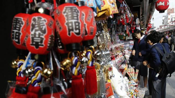 Visitors look at items outside a souvenir store at Nakamise shopping street in Asakusa district in Tokyo