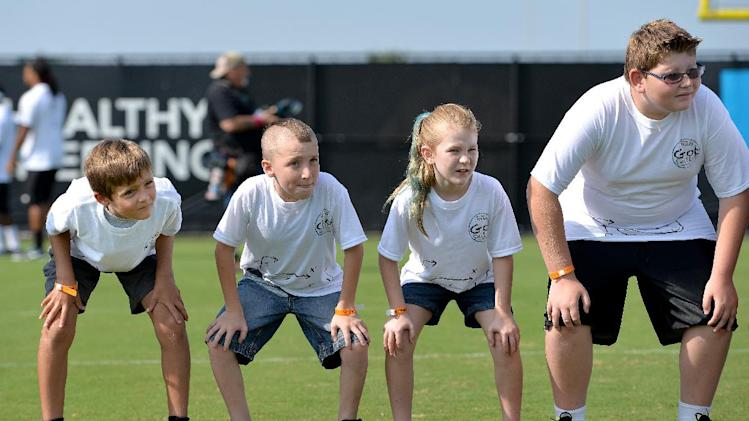 The kids line up and practice their linebacker stance at an NFL football Jacksonville Jaguars' Got Skills Rookie Day on Friday, June 20, 2014, in Jacksonville, Fla