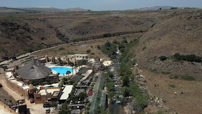 This picture taken on Thursday May 23, 2013 shows a general view of a resort near the Lebanon-Israel border, at the right side of the river, in the border village of Wazzani, south Lebanon. The $3 million complex was built in the shape of a fort includes luxury chalets, swimming pools and a sprawling restaurant, located at the foothills of the Israeli-occupied Golan Heights. Israeli soldiers often walk up to the other side of the river to gawk at the guests having lunch while dipping their feet in the river. Lebanese businessmen are building resorts and restaurants with an aim to attract tourists to the border area that was cut off form the rest of the country until Israel's withdrawal in 2000. (AP Photo/Hussein Malla)