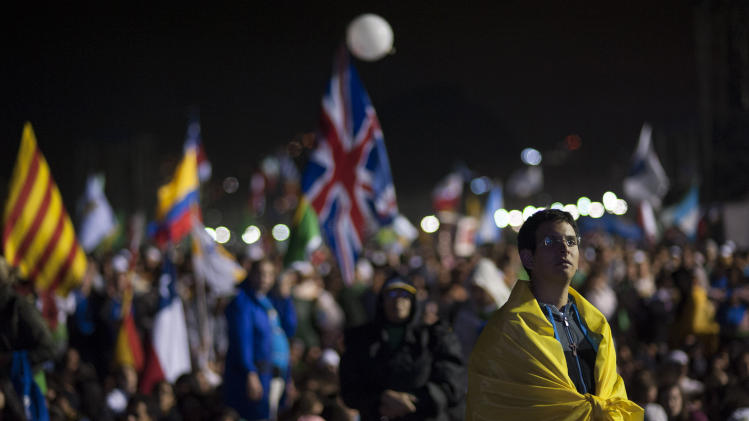 A pilgrim wrapped in a Brazilian national flag watches as Catholic youth gather on Copacabana Beach for the inaugural World Youth Day Mass in Rio de Janeiro, Brazil, Tuesday, July 23, 2013. As many as 1 million young people from around the world are expected in Rio for the Catholic youth event. (AP Photo/Nicolas Tanner)