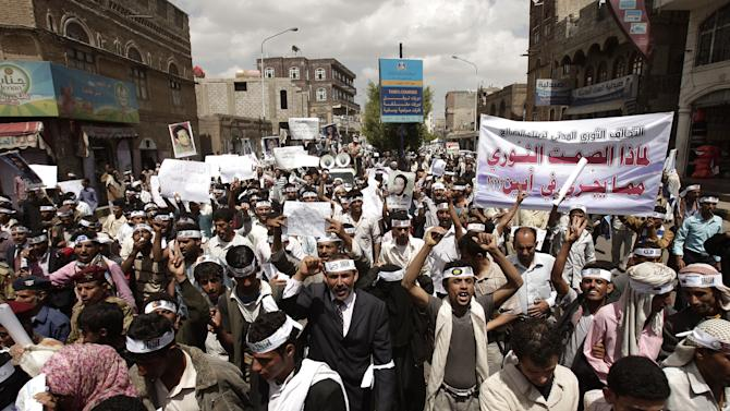 """Yemeni members of the Peaceful Revolution Salvation Front chant slogans during a demonstration demanding independence of the judicial system from government control,  in Sanaa, Yemen, Monday, April 23, 2012. Arabic on the banner reads, """"why the revolutionary silence toward what's happening in Abian."""", referring to the army action against al-Qaida in that area. (AP Photo/Hani Mohammed)"""