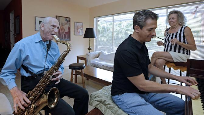 In this May 11, 2015 photo, Al Karp, left, plays the saxophone as he rehearses with his son Larry, center, and wife Saundra, right, at their home in North Miami Beach, Fla. The trio performs old standards locally as the Karp Family to ease stress and help raise money to save their home from foreclosure. (AP Photo/Alan Diaz)