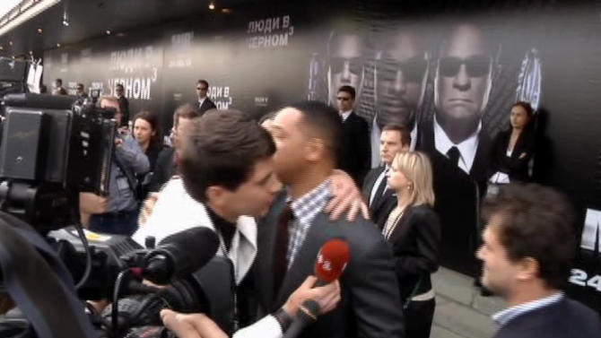 "FILE - In this video image taken from AP video on May 18, 2012, U.S. actor Will Smith, center right, is embraced by reporter Vitalii Sediuk, white suit, from the Ukrainian television channel 1+1 on the red carpet before the premiere of ""Men in Black III"" in Moscow. Smith later slapped Sediuk who tried to kiss him before the Moscow premiere. Sediuk's antics have left him with fewer friends in the entertainment world after his publicist and television station cut ties with him over pranks that have once again landed the 25-year-old in handcuffs. He's kissed Will Smith in Moscow, tried to steal Adele's spotlight at the Grammys, dove under America Ferrera's dress at Cannes and now accosted Brad Pitt on the red carpet of a Hollywood premiere. (AP Photo via AP video, File)"
