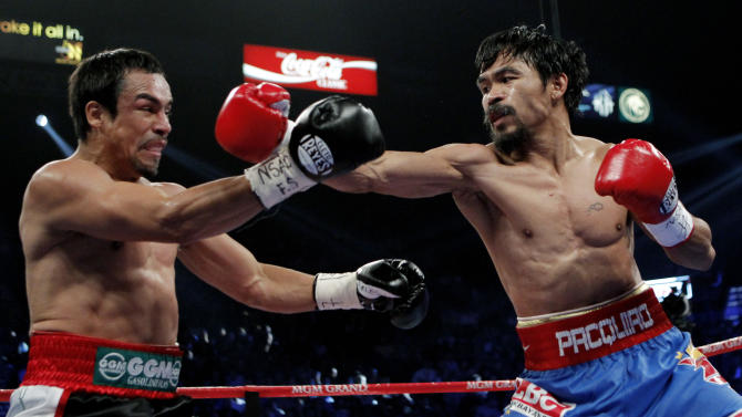 Manny Pacquiao, right, of the Philippines, hits Mexico's Juan Manuel Marquez during a WBO welterweight title fight Saturday, Nov. 12, 2011, in Las Vegas. (AP Photo/Jae C. Hong)