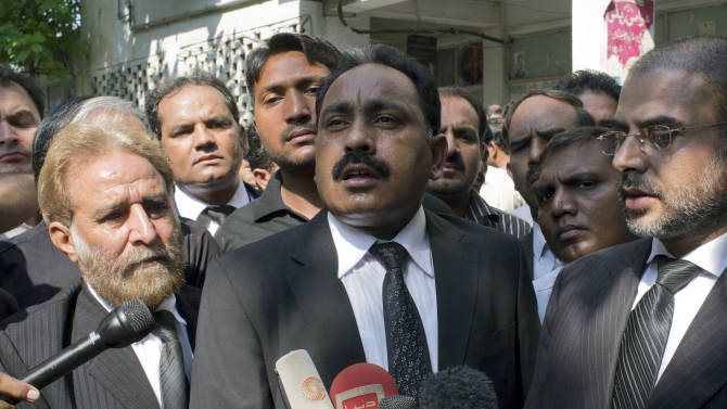 Tahir Naveed Chaudhry, center, the lawyer of a Christian girl accused of blasphemy, briefs reporters about a court proceeding in Islamabad, Pakistan on Thursday, Aug. 30, 2012. A judge hearing the case has delayed a bail hearing after a lawyer representing the man accusing the girl of burning the Quran challenged a medical report putting the girl's age at 14. (AP Photo/B.K. Bangash)