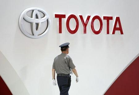 Security guard walks under the logo of toyota motor corp at the