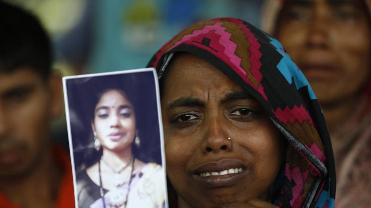 A woman holds a picture of her relative, a garment worker who went missing in the Rana Plaza collapse, on the first year anniversary of the accident, at a school in Savar