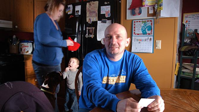 This Jan. 16, 2013 photo, Mike Cooley, one of 59 workers laid off from the Decker Coal mine along the Montana-Wyoming border, poses for a photo while discussing his future job prospects at his house in Sheridan, Wyo., with his wife and 2-year-old son, in the background. Hundreds of millions of tons of coal remain at Decker, in the heart of the nation's largest coal-producing region, but slackening demand prompted its owners to lay off almost half its workers this month. (AP Photo/Matthew Brown)