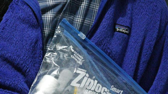 A traveler passing through a security check point holds his Ziploc bag at Portland International Airport Tuesday, May 8, 2012, in Portland, Ore.  Airport security procedures, with their intrusive pat downs and body scans, don't need to be toughened despite the discovery of a new al-Qaida airline bomb plot using more sophisticated technology than an earlier attempt, congressional and security officials said Tuesday. (AP Photo/Rick Bowmer)