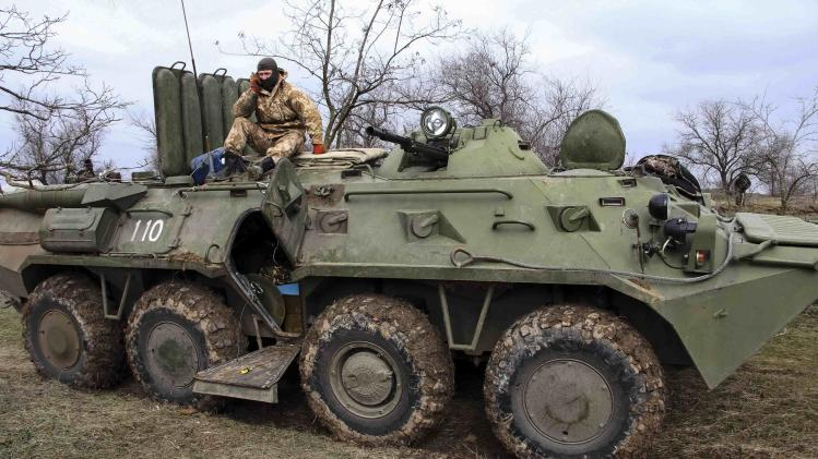 Ukrainian soldier sits on a military vehicle at a checkpoint at the road near a Crimea region border