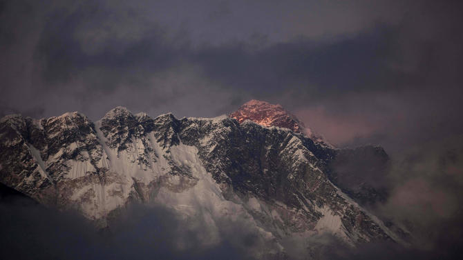 "FILE – In this Oct. 27, 2011 file photo, the last light of the day sets on Mount Everest as it rises behind Mount Nuptse as seen from Tengboche, in the Himalaya's Khumbu region, Nepal. The Everest climbing season began March 2014 with new rules that require climbers to bring down at least eight kilograms (17.6 pounds) of their personal garbage, and more security officials at the mountain's base camp to help climbers. More than 4,000 climbers have scaled the 8,850-meter (29,035-foot) summit since it was conquered in 1953 by Edmund Hillary and his Sherpa guide Tenzing Norgay. Over the years, climbers have left tons of garbage on the slopes on the mountain, and some have called it the ""world's highest garbage dump."" (AP Photo/Kevin Frayer, File)"