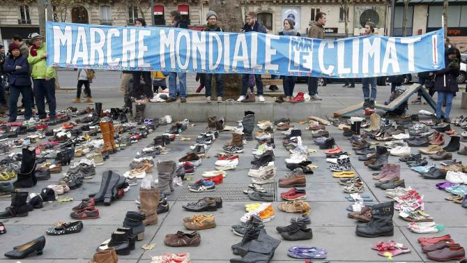 "A banner which reads ""Global Climate March"" is displayed in front of pairs of shoes symbolically placed on the Place de la Republique ahead of the World Climate Change Conference 2015 in Paris"