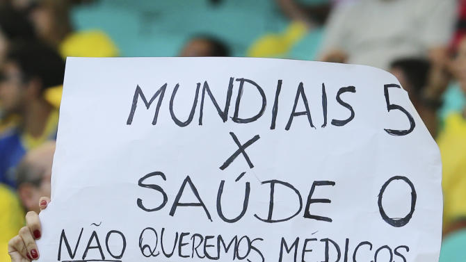 """A woman holds poster reading """"World 5 - Health 0. We don't want foreign doctors, we want resources"""" referring to the planned reform of the Brazilian health system prior to the soccer Confederations Cup group A match between Italy and Brazil at Fonte Nova stadium in Salvador, Brazil, Saturday, June 22, 2013. (AP Photo/Antonio Calanni)"""