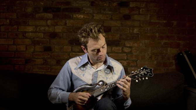 "In this Sept. 17, 2012 photo provided by the Chicago-based John D. and Catherine T. MacArthur Foundation, Chris Thile, 31, a mandolinist and composer who is creating a new musical aesthetic and a distinctly American canon for the mandolin through a lyrical fusion of traditional bluegrass orchestrations with a range of styles and genres, is seen in his East Village apartment in New York. Thile is among 23 recipients of this year's MacArthur Foundation ""genius grants."" (AP Photo/Courtesy of the John D. and Catherine T. MacArthur Foundation, Christopher Lane)"