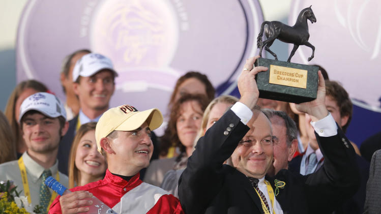Jockey Brian Hernandez Jr., left, looks on as Fort Larned trainer Ian Wilkes holds up the trophy after winning the running of the Breeders' Cup Classic horse race, Saturday, Nov. 3, 2012, at Santa Anita Park in Arcadia, Calif. (AP Photo/Jae C. Hong)
