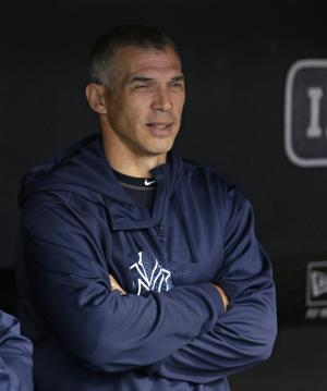 New York Yankees manager Joe Girardi looks out from the dugout as rain falls before a scheduled baseball game between the Yankees and the Cleveland Indians, Thursday, April 11, 2013, in Cleveland. The game was delayed due to rain. (AP Photo/Tony Dejak)