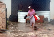 A woman wades through flood water brought by Hurricane Sandy as she evacuates her home in the Caribbean Terrace neighborhood of eastern Kingston, Jamaica, Wednesday, Oct. 24, 2012. Hurricane Sandy pounded Jamaica with heavy rain as it headed for landfall near the country&#39;s most populous city on a track that would carry it across the Caribbean island to Cuba, and a possible threat to Florida. (AP Photo/Collin Reid)