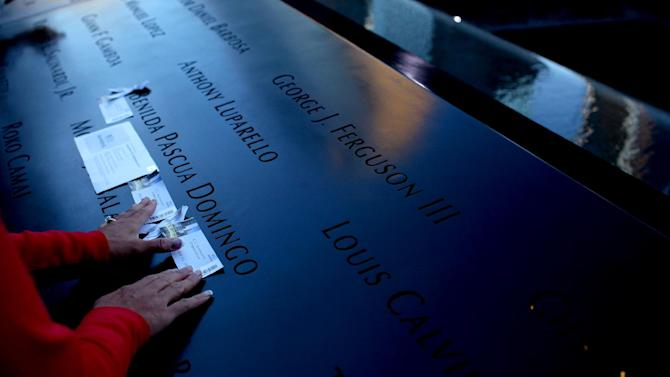 Family members of Belinda Pascua Domingo of New York place mementos on her name during observances held on the eleventh anniversary of the attacks on the World Trade Center, at the site in New York, September 11, 2012. (AP Photo/Craig Ruttle, Newsday, Pool)