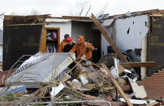 Residents clean up their damaged house in Marysville, Ind., Saturday, March 3, 2012. Massive thunderstorms, predicted by forecasters for days, threw off dozens of tornadoes as they raced Friday from t