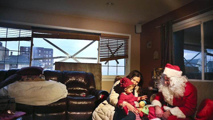 """In this Tuesday, Dec. 18, 2012 photo, Elizabeth Sampol holds her daughter, Ella, 14 months, who received a toy from Michael Sciaraffo as """"Santa"""", in the Belle Harbor section of the Queens borough of New York. Using Facebook, Sciaraffo started a charitable enterprise to collect and personally deliver toys to children affected by superstorm Sandy, dressed as Santa Claus.  (AP Photo/Bebeto Matthews)"""