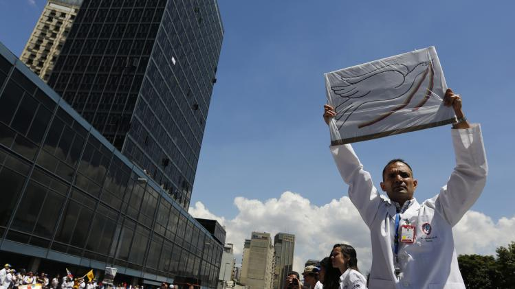 Anti-government doctor holds up a placard with a picture of a peace dove during a march to demand medical supplies for hospitals in Caracas