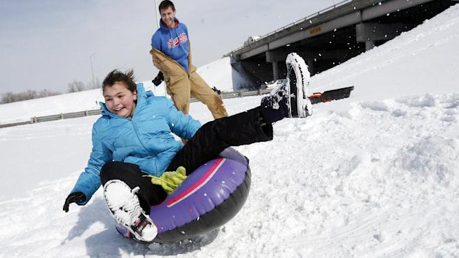 Taylor Bisbee, 12, gets some air while sledding with Jimmy Belcher on Tuesday morning, Feb. 26, 2013, at the hill at the K-61 and Avenue A overpass in Hutchinson, Kan. For the second time in a week, a major winter storm paralyzed parts of the nation's midsection Tuesday, dumping a fresh layer of heavy, wet snow atop cities still choked with piles from the previous system and making travel perilous from the Oklahoma panhandle to the Great Lakes. (AP Photo/The Hutchinson News, Lindsey Bauman)