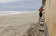 With a mandatory evacuation in place, the beach is deserted as Brad Bradley boards up the windows of a restaurant in anticipation of the arrival of Hurricane Irene in Nags Head, N.C., Friday, Aug. 26, 2011 on North Carolina's Outer Banks. (AP Photo/Charles Dharapak)