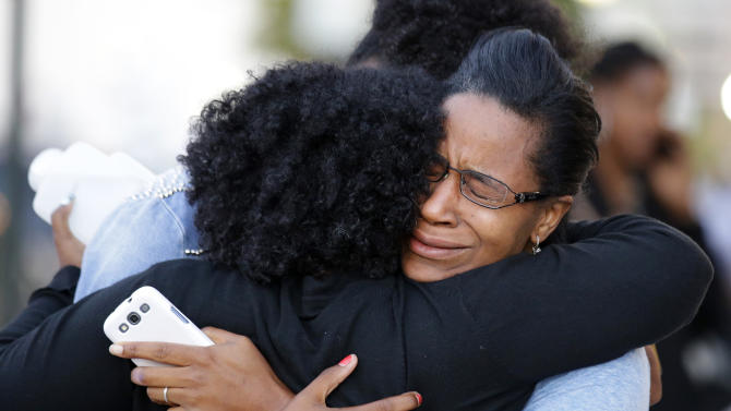Three women embrace near Nationals Park where family members waited to greet loved ones that were at the Washington Navy Yard, Monday Sept. 16, 2013, in Washington. At least one gunman launched an attack inside the Washington Navy Yard, spraying gunfire on office workers in the cafeteria and in the hallways at the heavily secured military installation in the heart of the nation's capital, authorities said. (AP Photo/Alex Brandon)
