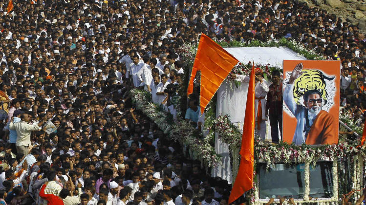 Indian mourners walk beside a truck carrying the body of Hindu hardline Shiv Sena party leader Bal Thackeray during his funeral in Mumbai, India, Sunday, Nov. 18, 2012. Thackeray, the extremist leader linked to waves of mob violence against Muslims and migrant workers in India, died Saturday after an illness of several weeks. He was 86. (AP Photo/Rafiq Maqbool)