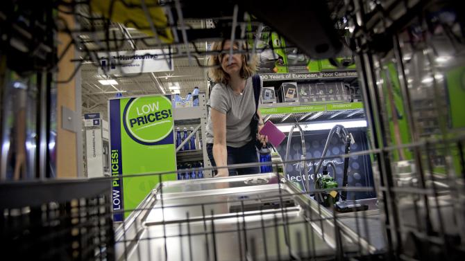 """FILE - In this Tuesday, June 19, 2012 file photo, Lauren Jonker opens up a dishwasher on display at a Lowe's store in Atlanta. During the recession, retailers used sales to lure cash-strapped Americans into stores. But that strategy has backfired. It has bred a group of deal junkies that won't shop unless they see """"70 percent"""" signs or yellow clearance stickers. (AP Photo/David Goldman, File)"""
