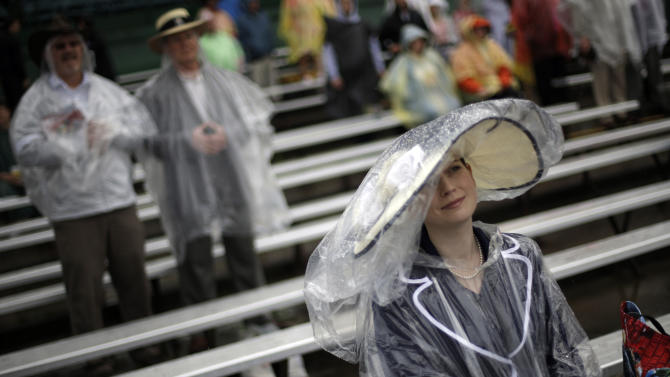 Spectators wait in the rain for the next race during the 139th Kentucky Derby at Churchill Downs Saturday, May 4, 2013, in Louisville, Ky. (AP Photo/David Goldman)