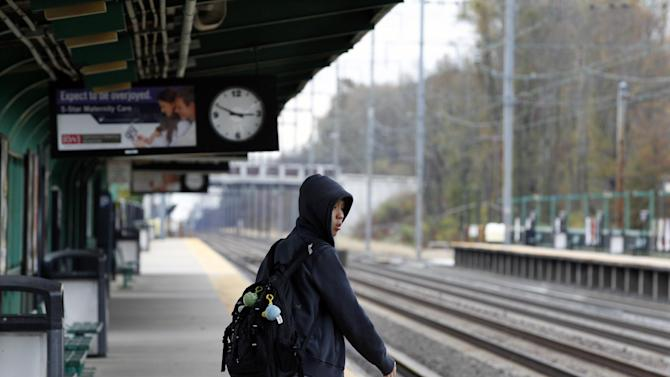 Josh Lin, 21, looks for an New Jersey Transit commuter train as he stands alone on the platform Thursday, Nov. 1, 2012, in Princeton Junction, N.J. There still is no train service after Monday's storm surge from superstorm Sandy knocked out power, caused flooding and toppled trees. Planes were getting up to speed faster than trains and automobiles in the storm-stricken Northeast. The region's major airports were all open once New York's LaGuardia resumed flights Thursday morning. While there were additional canceled flights and the tri-state air space was still relatively empty, flying was closer to normalcy than moving by rail, subway or car. (AP Photo/Mel Evans)