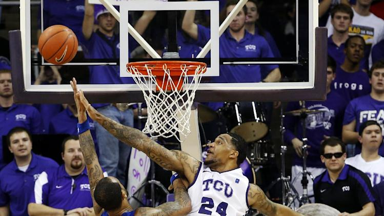 Kansas guard Travis Releford, left, shoots as TCU forward Adrick McKinney, center, defends during the second half of an NCAA college basketball game, Wednesday, Feb. 6, 2013, in Fort Worth, Texas. TCU won 62-55. (AP Photo/Sharon Ellman)