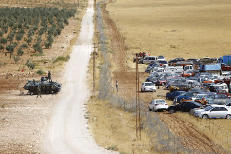 Turkish military vehicle stands next to Turkish-Syrian border as Kurdish Syrian refugees gather near town of Suruc