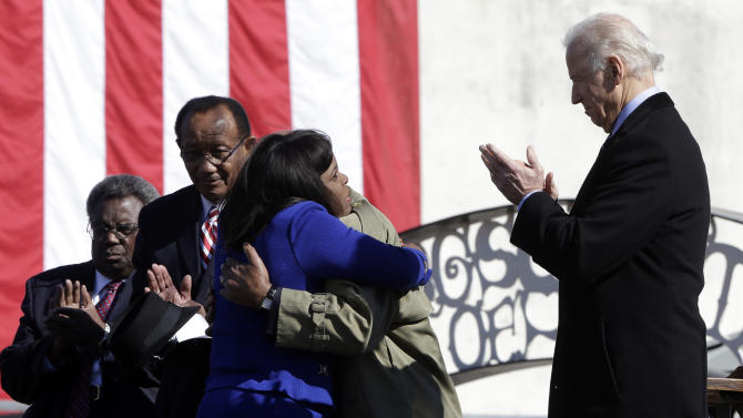 Vice President Joe Biden, right, applauds as U.S. Rep. Terri Sewell, D-Ala., hugs U.S. Rep. John Lewis, D-Ga., after introducing him in Selma, Ala., Sunday, March 3, 2013. Lewis was about to make remarks prior to the Bridge Crossing Jubilee on the 48th anniversary of Bloody Sunday when Alabama State Troopers beat civil rights marchers crossing the Edmund Pettus Bridge. At left is State Sen. Hank Sanders, D-Selma and Selma Mayor George Evans. (AP Photo/Dave Martin)