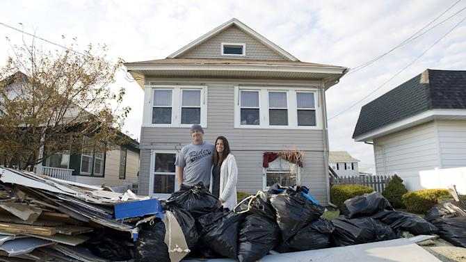 Jared and Sarah Lenko stand in front of their Ocean City, N.J. house on Saturday, Nov. 10 2012 that was under two feet of water during Superstorm Sandy. (AP Photo/The Press of Atlantic City, Matthew Strabuk)