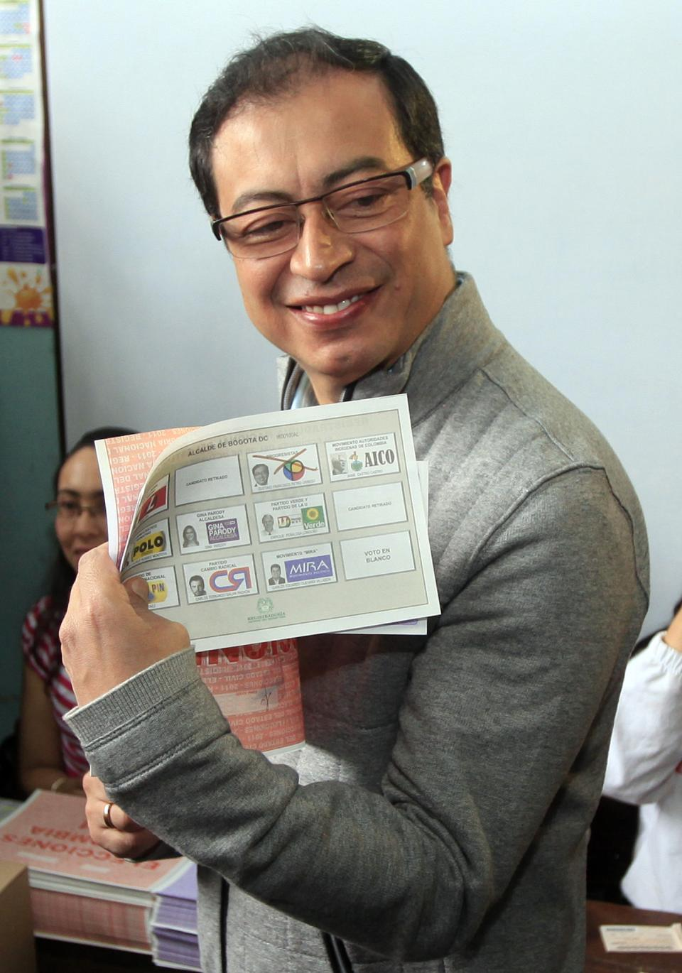 Gustavo Petro, left, Progressive party's candidate for Mayor of Bogota, shows his ballot during local and regional elections in Bogota, Colombia, Sunday, Oct. 30, 2011. Colombians go to the polls Sundays to choose mayors, state governors and local assemblies. (AP Photo/Fernando Vergara)